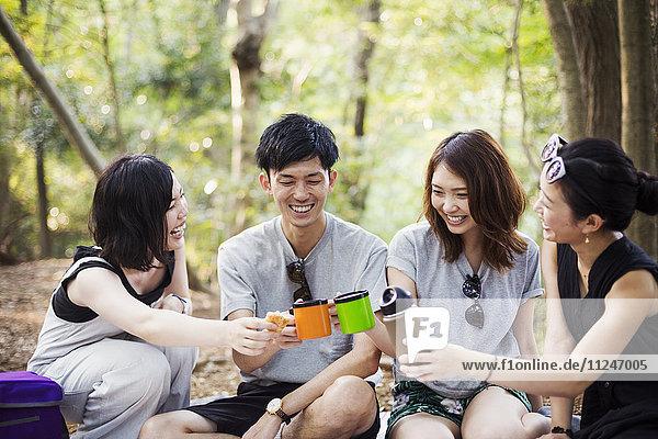 Drei junge Frauen und ein Mann sitzen in einem Wald.
