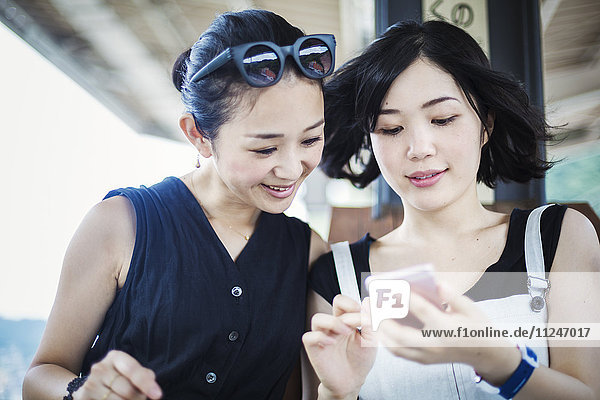 Two young women looking at a mobile phone.