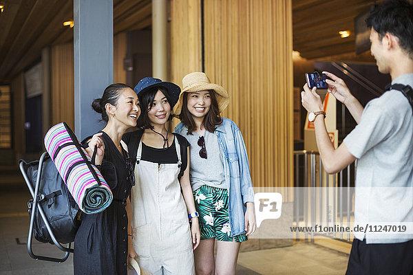 Mann  der drei junge Frauen fotografiert.