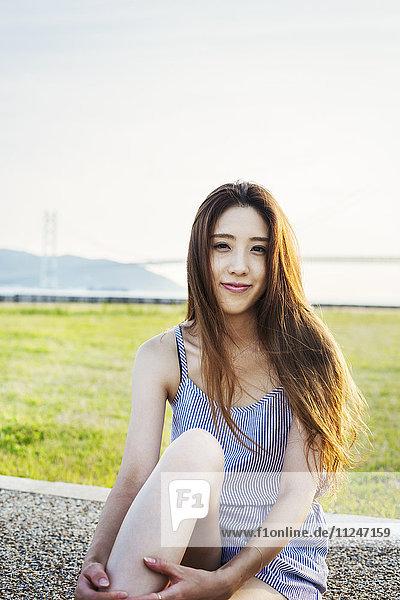 Bildnis einer lächelnden jungen Frau mit langen braunen Haaren.