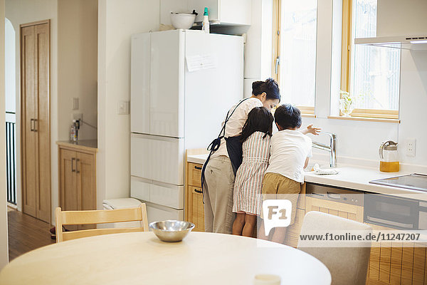 Familienhaus. Eine Mutter und zwei Kinder stehen an der Spüle in einer Küche.