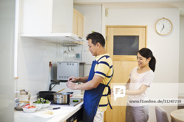 Family home. A man and woman  a wife tying her husband's apron in their kitchen.