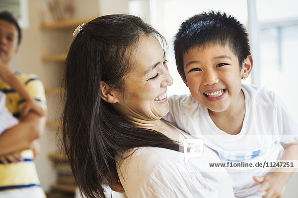Familienhaus. Eine Mutter  die ihren Sohn hält  und ein Vater  der seine Tochter hält.