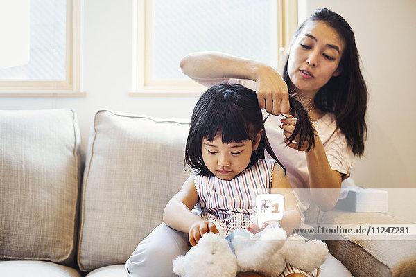Familienhaus. Eine Mutter kämmt das Haar ihrer Tochter.