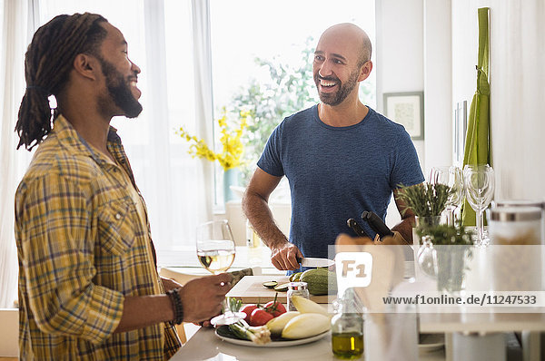 Smiley homosexual couple drinking wine in kitchen