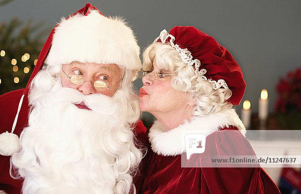 Mrs. Claus kissing Santa on cheek