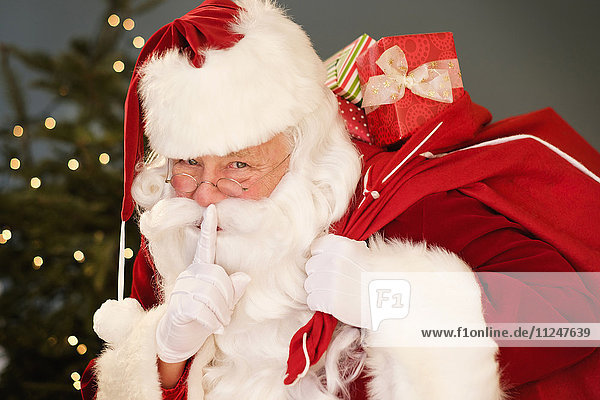 Portrait of Santa Claus with finger on lips  carrying sack over shoulder