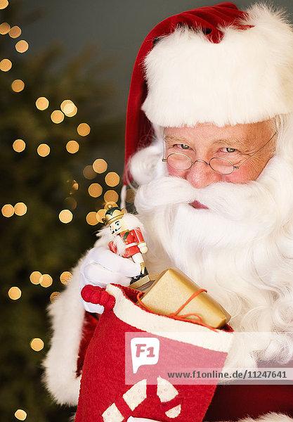 Portrait of Santa Claus holding nutcracker toy