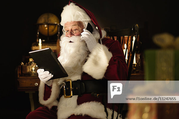 Santa Claus using digital tablet and talking by mobile phone