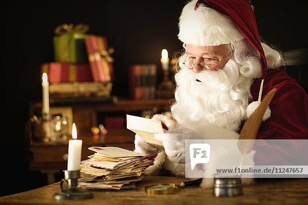 Portrait of Santa Claus reading child's letter at desk