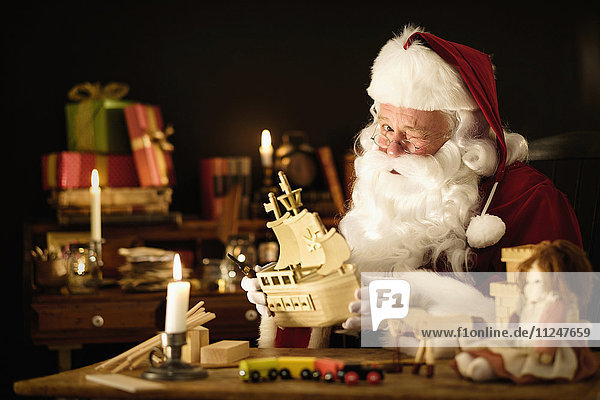 Santa Claus making wooden toy and winking