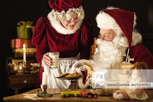 Mrs. Claus bringing homemade cookies to Santa Claus