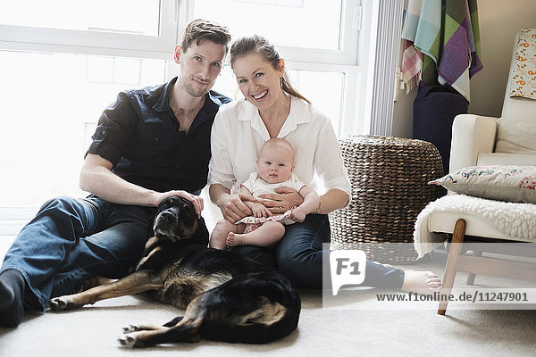 Portrait of happy family sitting on carpet with daughter (2-5 months) and dog