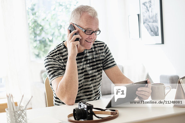 Man in home office using smartphone and tablet