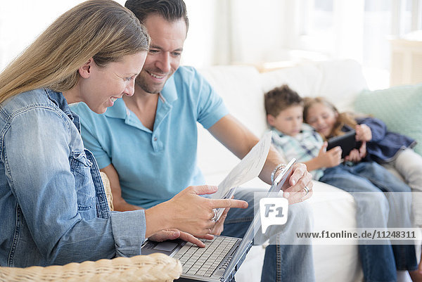 Man and woman paying bills with two children (6-7  8-9) sitting on sofa  using digital tablet