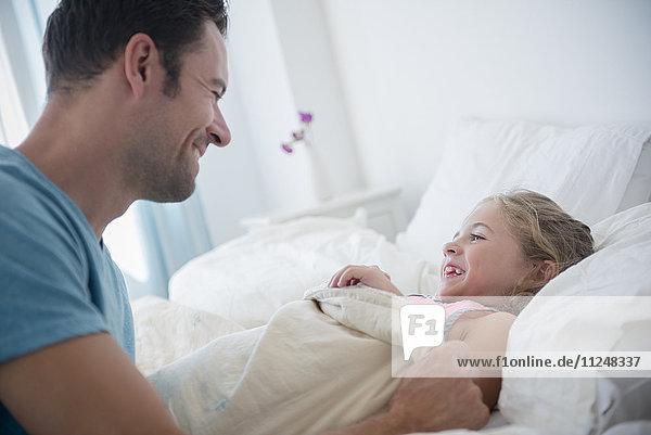 Father tucking daughter (6-7) in bed