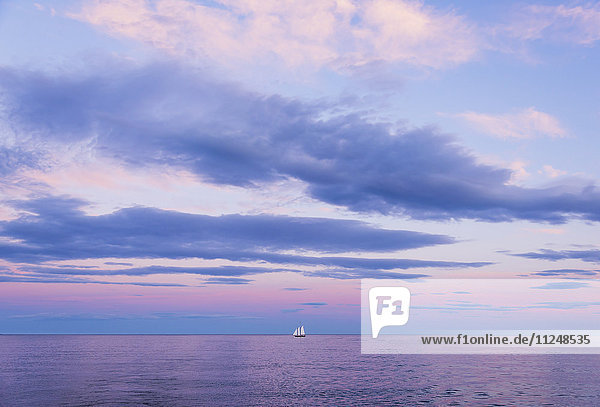 Pastel-colored sunset seascape with sailboat Pastel-colored sunset seascape with sailboat