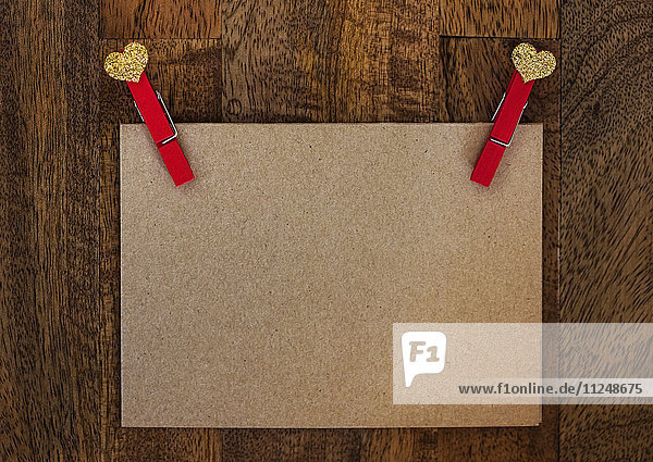 Blank paper with clothespin on wood Blank paper with clothespin on wood