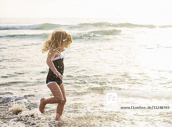 Girl (4-5) running in water on beach
