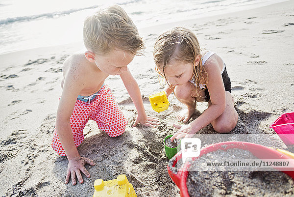 Boy (6-7) and girl (4-5) playing with sand on beach Boy (6-7) and girl (4-5) playing with sand on beach