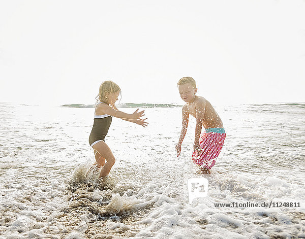 Mother walking with boy (6-7) and girl (4-5) on beach by water