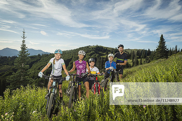 Family with children (10-11  12-13  14-15) with bicycles in mountain