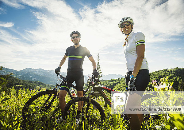 Mature couple during bicycle trip in mountain scenery