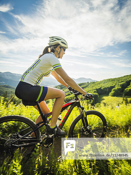 Woman during bicycle trip in mountain scenery