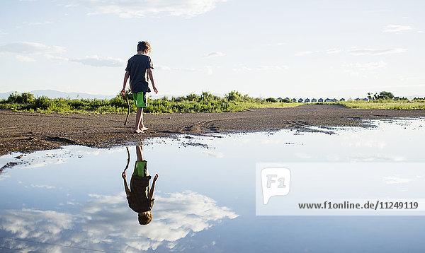 Boy (6-7) walking on lake shore