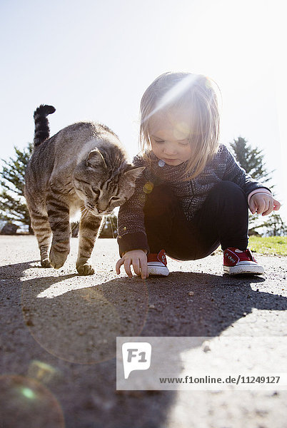 Crouching girl (2-3) and cat