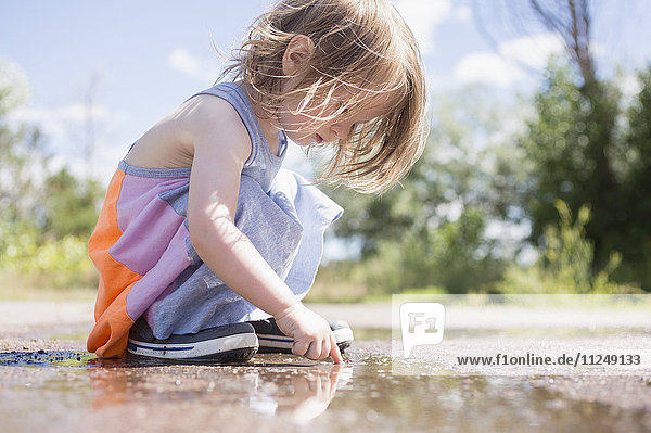 Portrait of girl (2-3) playing in puddle