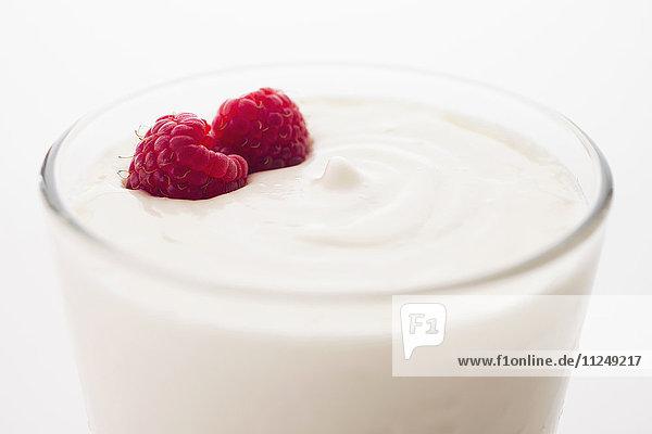 Yogurt with raspberries in drinking glass