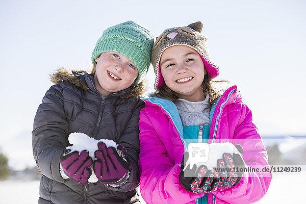 Portrait of girls (8-9  10-11) holding snow