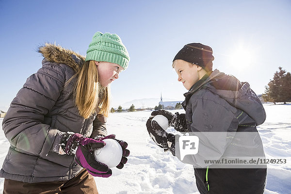 Children (8-9  10-11) playing with snowballs