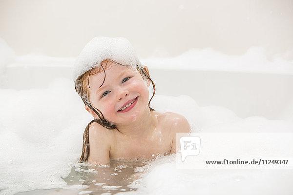 Smiling girl (4-5) having bubble bath