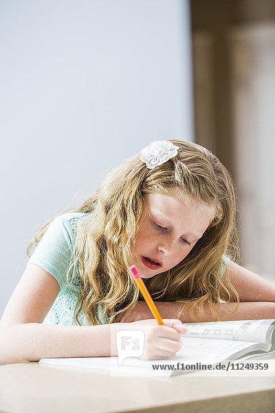 Blonde girl (8-9) doing homework at table