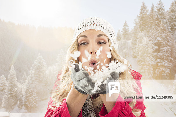 Young woman blowing snow off from hands