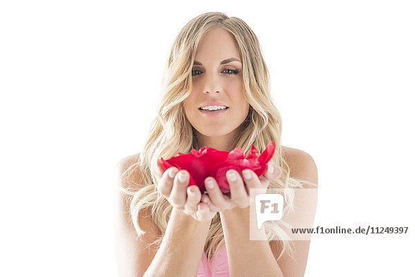 Young woman holding rose petals in hands