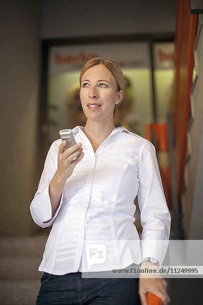 Woman wearing white shirt using mobile phone