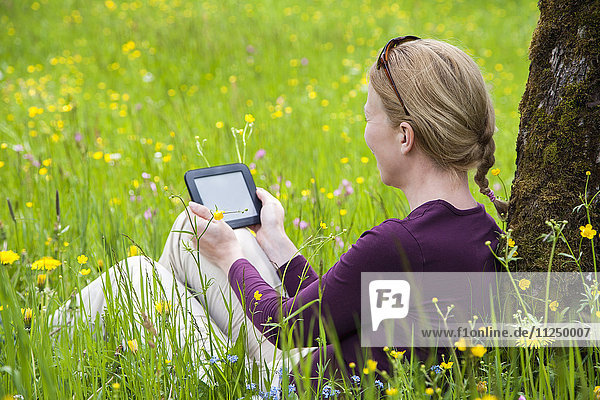 Woman using e-reader in meadow