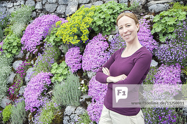 Smiling woman standing against flowerbed