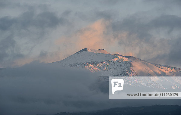 Snowcapped mountain at sunset