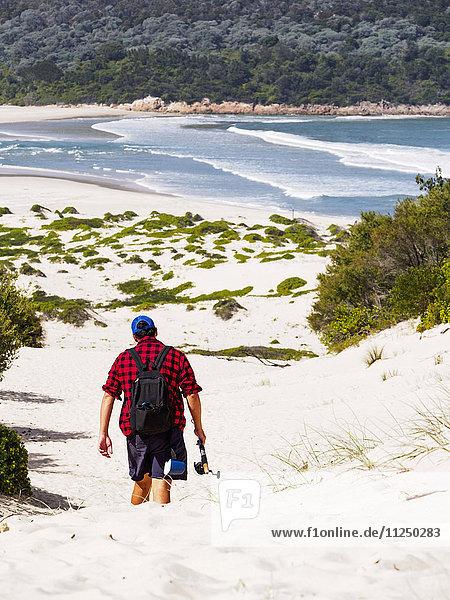 Mid adult man walking on beach