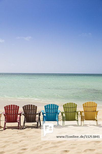 Caribbean  Netherland Antilles  Aruba  A row of colourful wooden deck chairs on Palm Beach