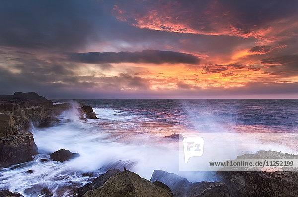 Isle of Skye Scotland. Big waves crashing into rocks at first light.