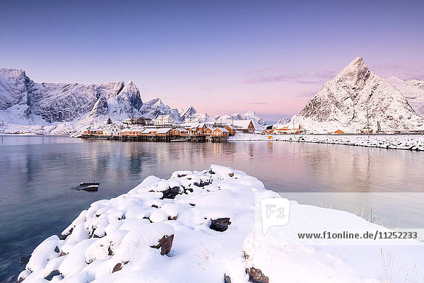 The colors of dawn frames the fishermen houses surrounded by snowy peaks Sakrisøy Reine Nordland Lofoten Islands Norway Europe