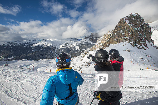 Skiers look at the Dolomites while skiing at Campitello di Fassa  Trentino  Italy  Europe