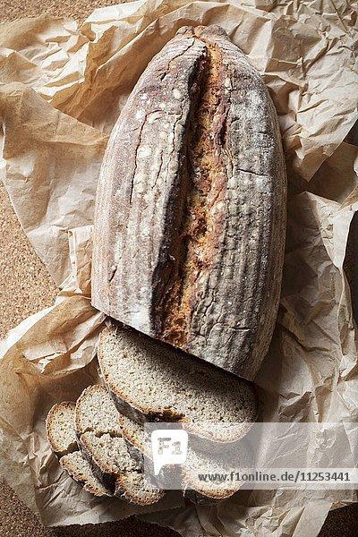 Angeschnittener Brotlaib auf Papier