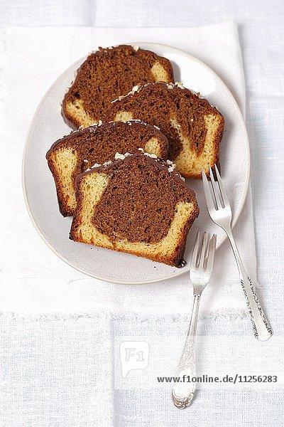 Mehrere Stücke Marmorkuchen mit Schokoladenglasur auf Teller