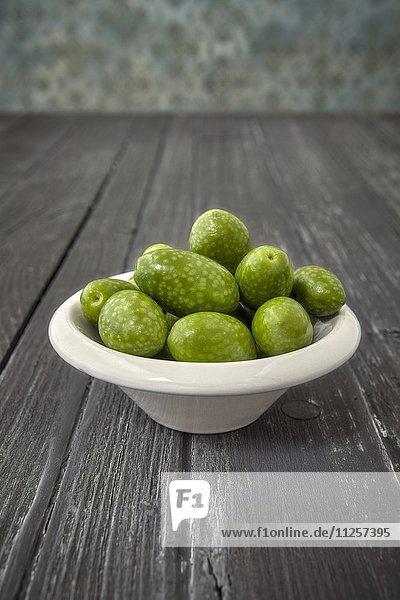 Oliven (Arbosana  Chile) im Schälchen auf Holzuntergrund
